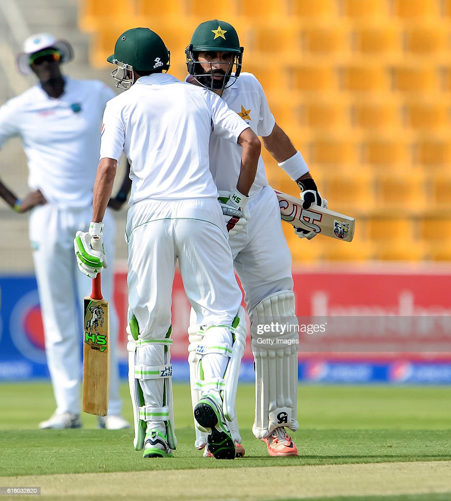 Misbah Ul Haq (R) congratulates Younis Khan (L) on his half century during Day One of the Second Test between Pakistan and the West Indies at the Zayed Cricket Stadium on October 21, 2016 in Abu Dhabi, United Arab Emirates.