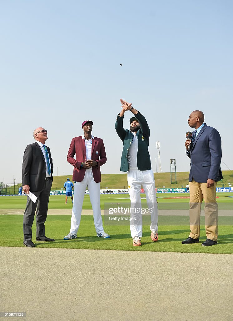 Misbah Ul Haq (middle right) flipping the coin for the toss during Day One of the Second Test between Pakistan and the West Indies at the Zayed Cricket Stadium on October 21, 2016 in Abu Dhabi, United Arab Emirates.