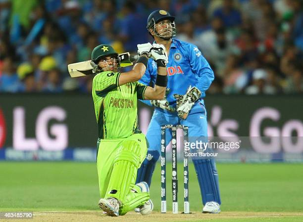 MisbahulHaq of Pakistan hits a boundary as wicketkeeper MS Dhoni of India looks on during the 2015 ICC Cricket World Cup match between India and...