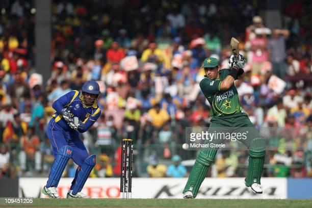 MisbahulHaq of Pakistan plays to the offside as wicketkeeper Kumar Sangakkara looks on during the Pakistan v Sri Lanka 2011 ICC World Cup Group A...