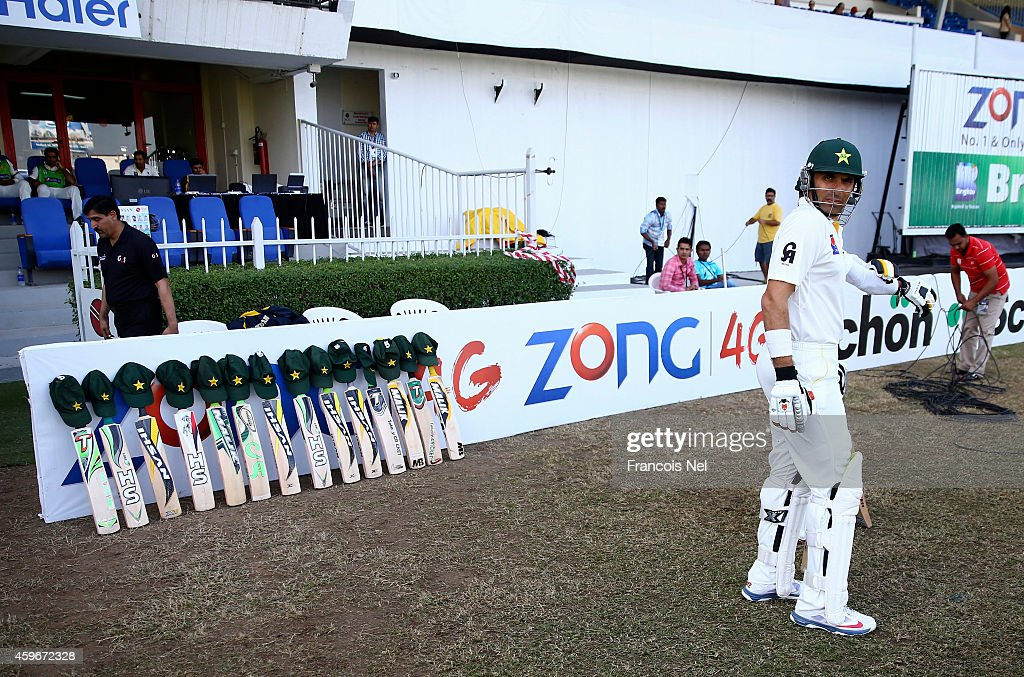 Misbah-ul-Haq of Pakistan walks past bats and caps placed outside the Pakistan dressing room in memory of Australian cricketer Phillip Hughes who died as a result of head injuries sustained during the Sheffield Shield match between South Australia and New South Wales at the SCG on Tuesday, at Sharjah Stadium on November 28, 2014 in Sharjah, United Arab Emirates.
