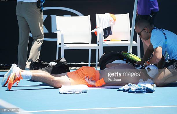 Mischa Zverev of Germany receives treatment on court from Self Wardini in his first round match against Guillermo GarciaLopez of Spain on day one of...