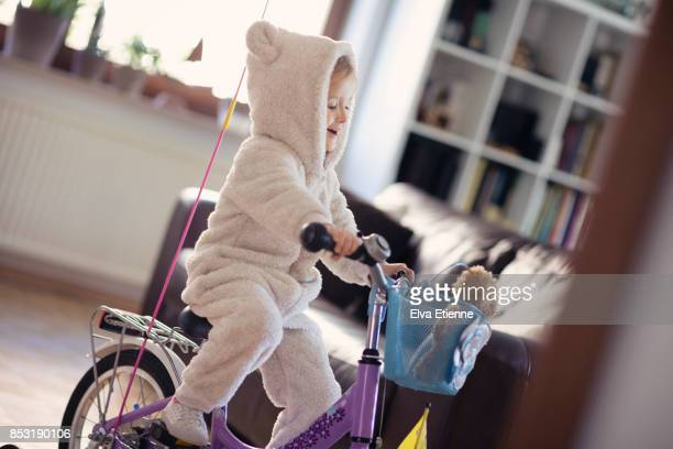 Mischievious child cycling through house on a bicycle