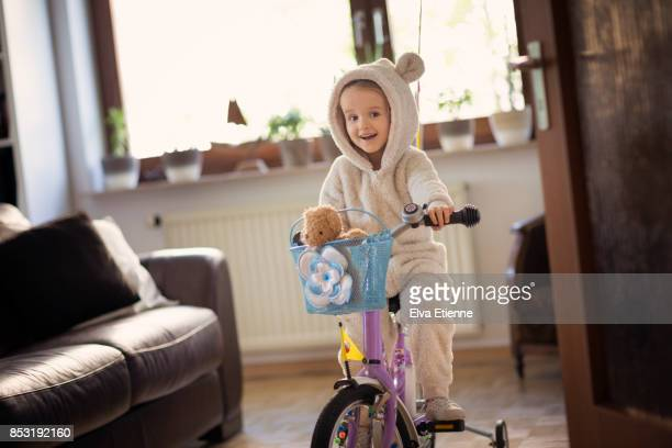 Mischievious child cycling through living room on a bicycle