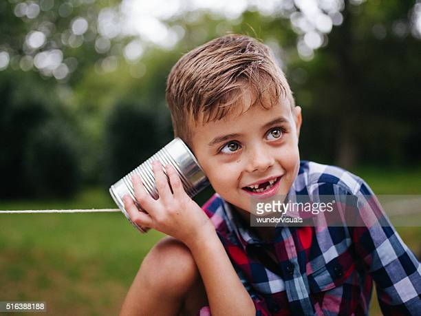 Mischievous Boy listening on tin can phone in his hands