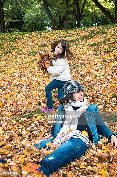 Mischievous daugther about to pitch autumn leaves on her mother.