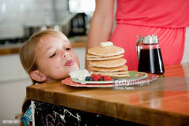 Mischievous girl gazing at pancakes on breakfast bar
