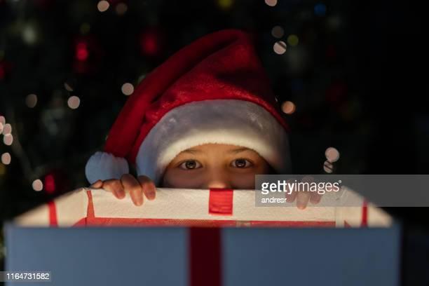 chica traviesa recibiendo un adelanto de su regalo de navidad - preestreno fotografías e imágenes de stock