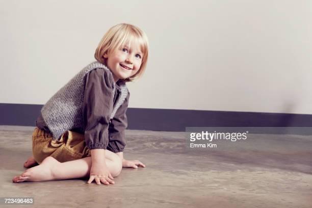 Mischievous girl kneeling on floor