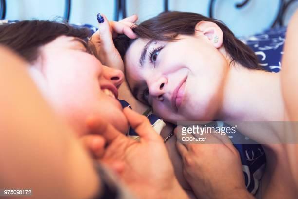 schelmischen lesben paar flirten im bett - intim piercing stock-fotos und bilder