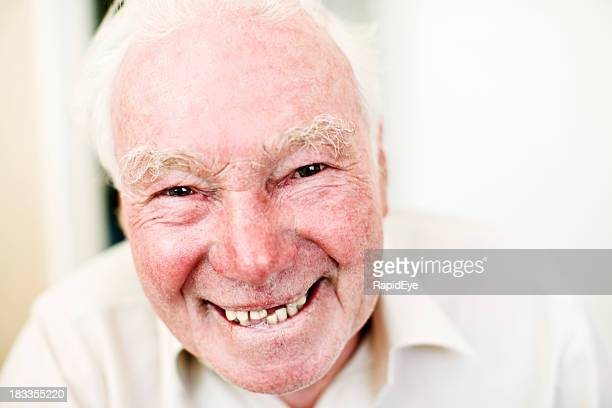Mischievous looking old man smiles cheekily