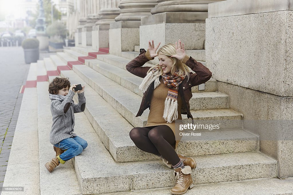 Mischievous mother with son on stairs : Bildbanksbilder