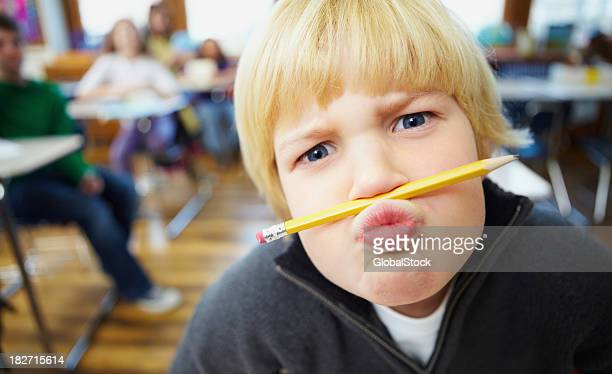 Mischievous school boy balancing a pencil on the nose