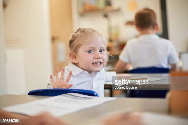 mischievous schoolgirl in classroom lesson at primary school - naughty kids in classroom stock photos and pictures