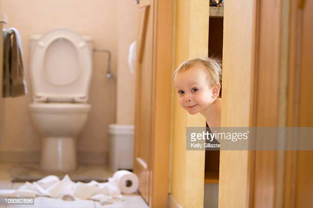 Mischievous toddler boy playing with toliet paper