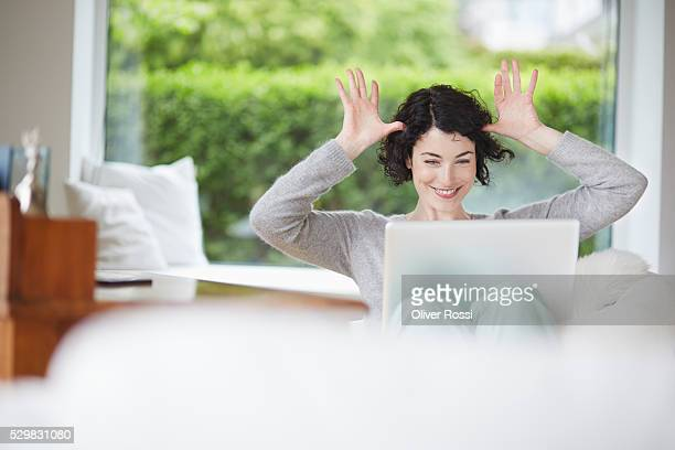Mischievous young woman using laptop at home