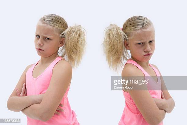 Miserable twin girls frowning, portrait