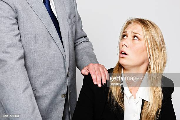 Miserable junge Geschäftsfrau sieht bei Mann berühren Ihre Schulter