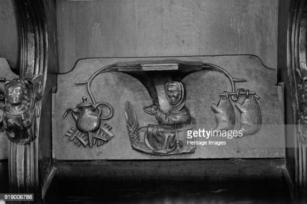 Misericord St Laurence's Church Ludlow Shropshire 1966 Detail of a carved wooden misericord depicting a man warming himself by the fire with two...