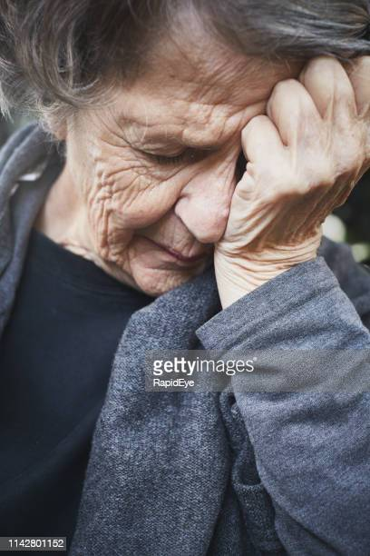 misery. a wrinkled old woman grimaces, holding her head - vulnerability stock pictures, royalty-free photos & images
