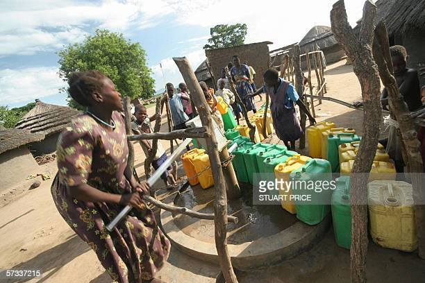 STORY Misery thrives in Uganda's camps for war displaced A woman pumps water from a borehole 10 April 2006 in Patongo internally displaced people's...