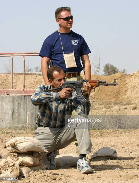 STORY 'IRAQUSSECURITY' Misha a team leader for a security company in Iraq gives shooting lessons to an Iraqi man 21 February 2004 at a shooting range...