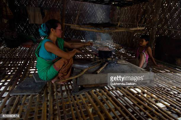 Mishing woman cooks food in their traditional bamboo hut The Mishings are the largest ethnic tribal community living in northeast India