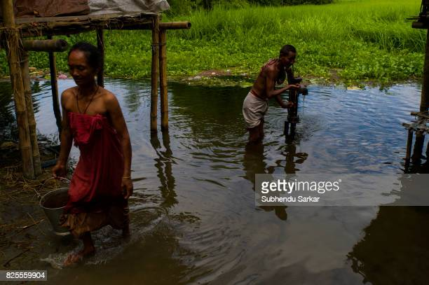 Mishing woman fetches water from a tubewell that is flooded by monsoon rain The Mishings are the largest ethnic tribal community living in the...
