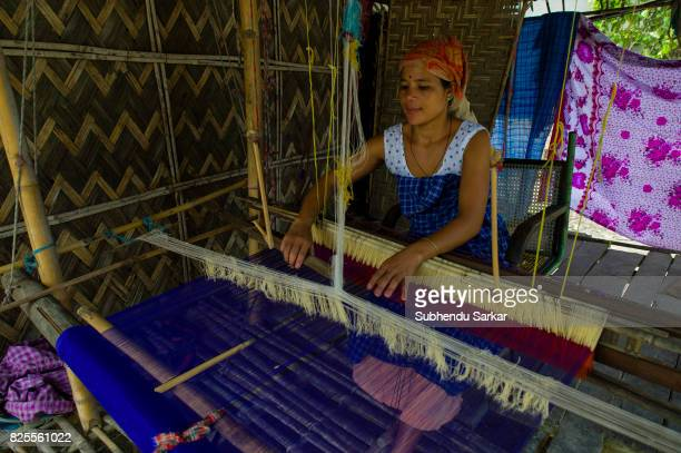 Mishing woman works at a handloom at her traditional hut The Mishings are the largest ethnic tribal community living in northeast India