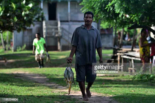 Miskito men carry fish on their way back home in Prumnitara Puerto Lempira Honduras on July 8 2019 Thousands of fishing divers of the Mosquitia...