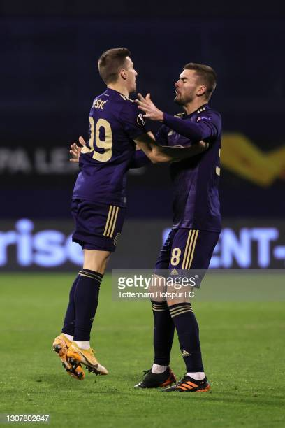 Mislav Orsic of GNK Dinamo Zagreb celebrates with Bartol Franjic after scoring their side's first goal during the UEFA Europa League Round of 16...