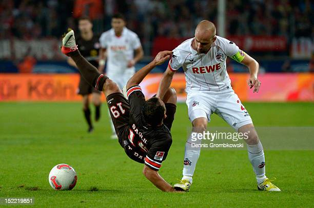 Miso Brecko of Cologne steps on the hand of Mahir Saglik of St Pauli as they battle for the ball during the Second Bundesliga match between 1 FC...