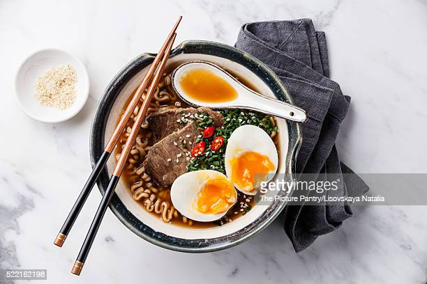Miso Ramen Asian noodles with beef and egg in bowl on white marb