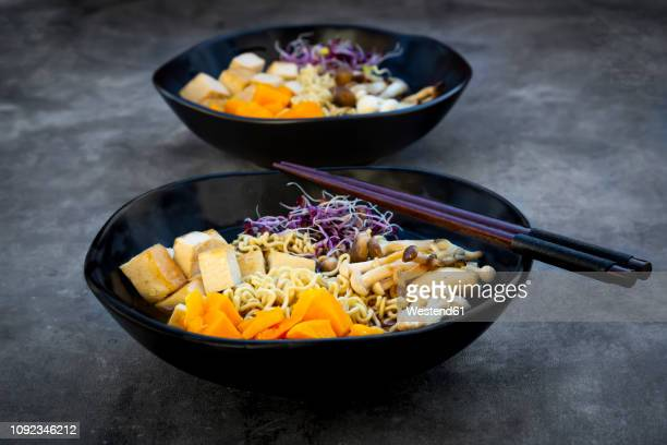 miso ramen soup with noodles, hokaido pumpkin, red radish sprouts, fried tofu, shimeji mushroom and king trumpet mushroom - japanische küche stock-fotos und bilder