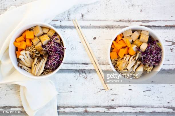 miso ramen soup with noodles, hokaido pumpkin, red radish sprouts, fried tofu, shimeji mushroom and king trumpet mushroom - king trumpet mushroom stock pictures, royalty-free photos & images