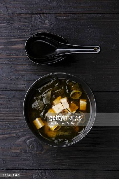 Miso Soup with tofu and wakame in bowl serving size on burned black wooden background