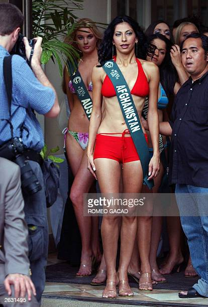 Miss Afghanistan Vida Samadzai steps out while Miss Australia Shivaune Christina looks on during the presentation of the 60 candidates for Miss Earth...