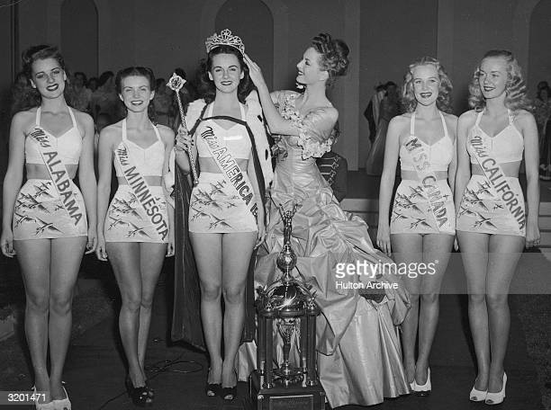 Miss America 1946 Marilyn Buferd crowns the new Miss America 1947, Barbara Jo Walker, of Memphis, Tennessee, as five other contestants smile,...
