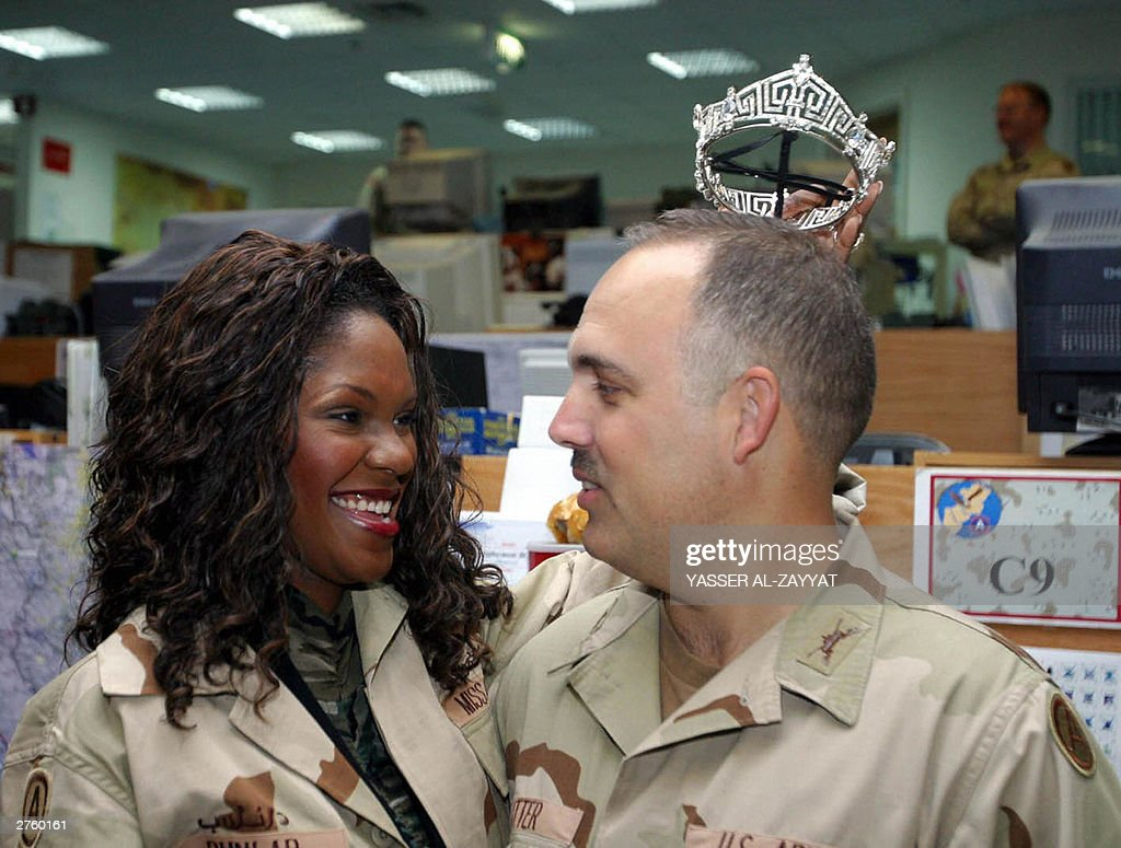 Miss America 2004 Ericka Dunlap jokes with a US soldier during her visit to Camp Doha, a major US military base north of Kuwait City, 25 November 2003. Dunlap's trip to spend Thanksgiving day with US troops in Kuwait marks the first time since the Vietnam War that a Miss America travels abroad to visit deployed US armed forces. This humanitarian mission is being sponsored and organised by Humanitarian Operations Center of Kuwait (HOC), a multi-national cooperative organization created to serve as a clearinghouse for humanitarian assistance to Iraq. AFP PHOTO/Yasser AL