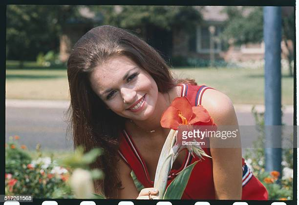 Miss America Phyllis George holds a flower