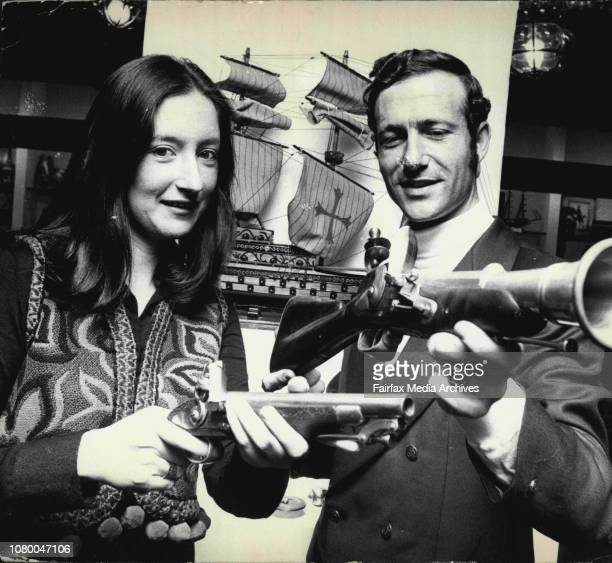 Miss Ann Nevans of Mosman is shown two reproducti tmm pieces of armoury by Mr Emile C Lopez General Manager of the Trade centre a Pistol and...