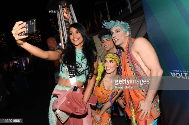 Miss Aruba Danna Garcia poses with members of Volta By Cirque Du Soleil cast members during Volta By Cirque Du Soleil at Atlantic Station on December...