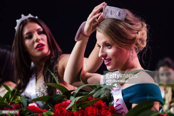 Miss Belarus Aleksandra Chichikova winner of the Miss Wheelchair World contest beauty pageant adjusts her crown with the helping hand of second...