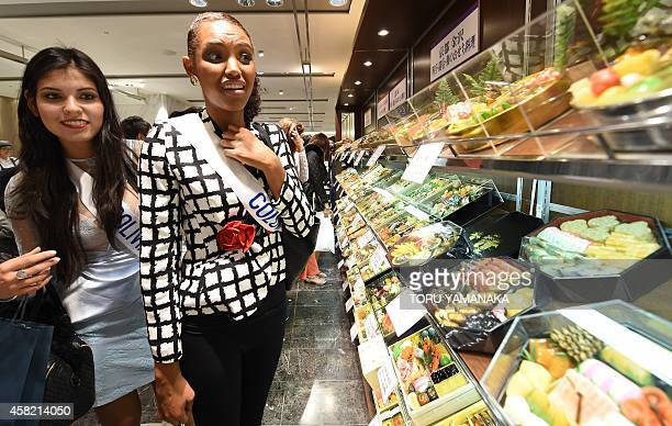 Miss Bolivia Joselyn Toro and Miss Colombia Zuleika Kiara Suarez Torrenegra look at food samples made from wax when they stroll through a food floor...