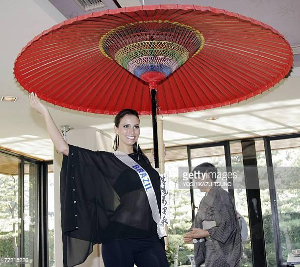 Miss Brazil Carolina Prates poses under a large parasol for tea ceremony during a visit to the Sankeien Japanese garden in Yokohama 07 October 2007...