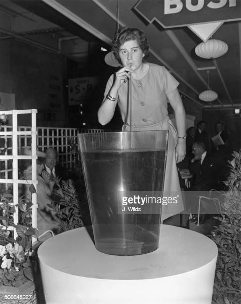 Miss Bush takes a long drink at the Brewing Bottling and Allied Trades Exhibition being held at Olympia London 3rd October 1960