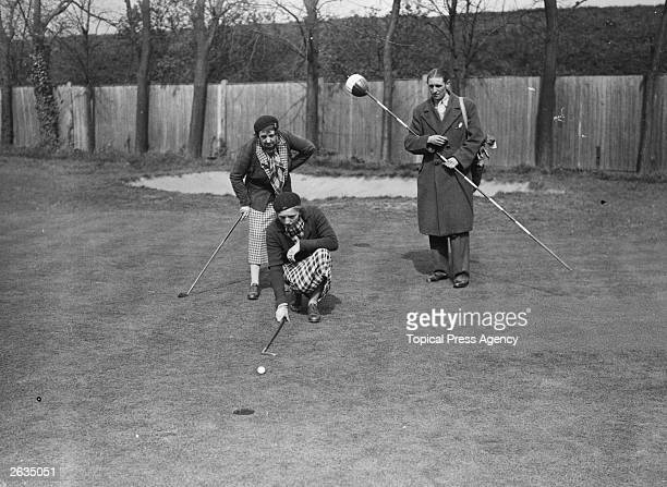Miss Diana Fishwick and her mother study the lie of the golf course in preparation for a putting shot They are taking part in the Women's golf at...