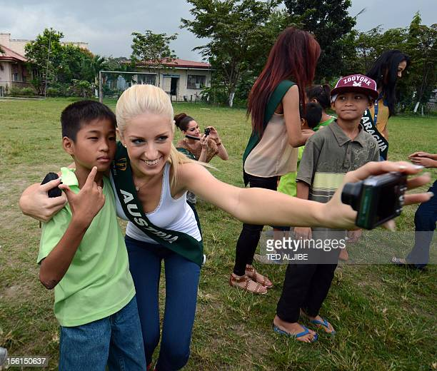 Miss Earth contestant Jenna Seymour of Australia poses for photo with a street child during a visit to a governmentrun shelter for street children in...