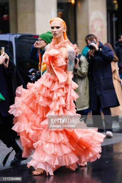 Miss Fame wears a salmon-color frilly ruffled long halter-dress, lustrous salmon-color satin long gloves, old-pink strappy heeled sandals, outside...