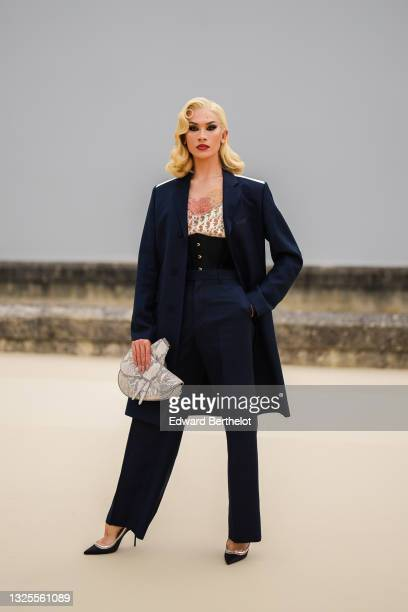 Miss Fame wears silver earrings, a beige mesh V-neck t-shirt with white Dior Oblique Jacquard embroidered, a navy blue long coat with white stripes...